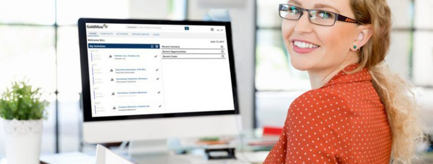 Woman in red blouse smiling in front of a desk with computer showing a screenshot of GoldMine CRM