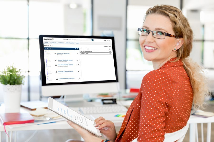 Woman in glasses at desk using GoldMine CRM