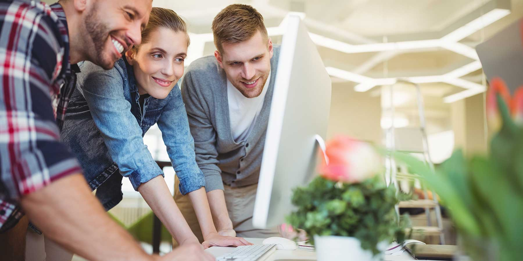 a woman and two men all in their twenties crowded around a desktop looking at the screen and smiling